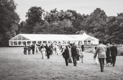 Black and White photo of a Wedding marquee with guests walking to the wedding