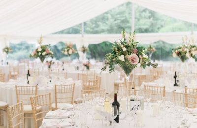 Clearspan marquee with round tables, limewash chairs and pink floral table centres.